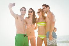 Happy friends taking a selfie on the beach Stock Photos