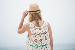 Cute blonde woman holding her straw hat on the beach Stock Photos