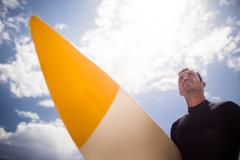 Surfer holding surfboard on beach on a sunny day Stock Photos