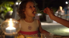 Mum feeds the child in the open-air restaurant in the evening. Stock Footage