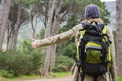 Hitch hiking woman with backpack in the countryside Stock Photos