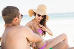 Boyfriends applying sun cream on girlfriend on the beach Stock Photos