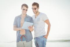 Friends looking at tablet on the beach Stock Photos
