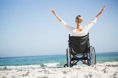 Woman in a wheelchair relaxing on the beach Stock Photos