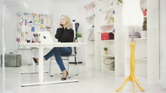 Stock Video Footage of 4K Fashion designer in her studio, working on laptop & talking on phone