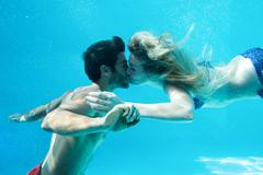 Happy couple kissing underwater in swimming pool Stock Photos