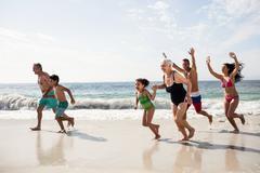Happy family walking on beach on a sunny day Stock Photos