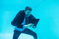 Businessman using tablet underwater in swimming pool Stock Photos