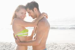 Happy couple embracing on the beach on a sunny day Stock Photos