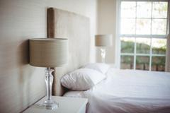 Lamp shades by bedroom against window Stock Photos