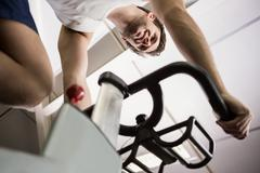 Low angle view of man working out on exercise bike at spinning class in gym Stock Photos