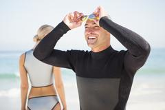 Handsome man wearing swimming cap and goggles with girlfriend in background Stock Photos