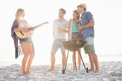 Cute group of friends having a barbecue and beers and playing the guitar Stock Photos
