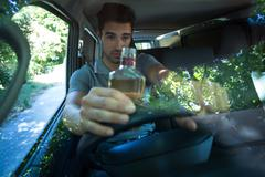 Slumped man drinking alcohol while driving car Stock Photos