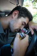 Close-up of slumped man holding alcohol bottle while sitting in car Stock Photos