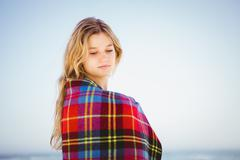 Peaceful blonde woman relaxing with blanket on the beach Stock Photos