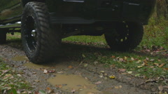 Lower to Truck Driving Through Mud Puddle Slow Motion Stock Footage