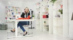4K Fashion designer in her studio, working on laptop & talking on phone - stock footage