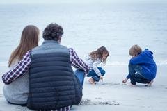 Parents looking at children writing on sea shore in beach Stock Photos