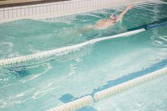 Swimmer doing a backstroke in the pool at leisure center Stock Photos