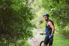 Portrait of man with bike standing on dirt road amidst trees in forest Stock Photos