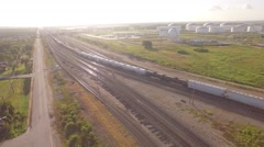 Pan Following Train Into Yard With Large Oil Storage in Background Stock Footage