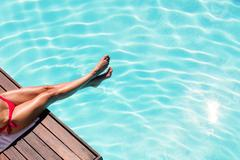 Woman enjoying sunbath on the pool edge on a sunny day Stock Photos