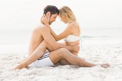 Happy couple sitting and embracing on the beach Stock Photos