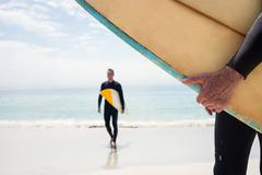 Man walking with surfboard on the beach on a sunny day Stock Photos