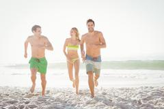 Happy friends running on the beach on a sunny day Stock Photos