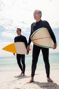 Father and son standing on the beach with surfboard and looking at a distance Stock Photos