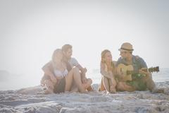 Cute group of friends sitting on the sand and playing the guitar on the beach Stock Photos