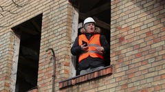 Angry site manager with tablet PC in building's second floor window - stock footage