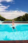 Woman diving into swimming pool on a sunny day Stock Photos