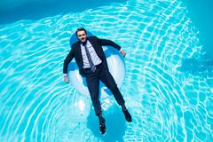 Businessman relaxing on inflatable in swimming pool Kuvituskuvat