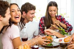 Group of friends having meal at home Stock Photos