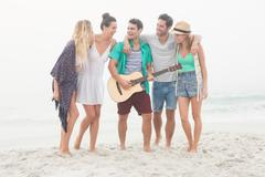 Cute group of friends playing the guitar on the beach Stock Photos