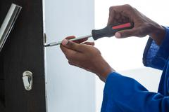 Man fixing the door handle with screwdriver at home Stock Photos