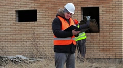 Site manager checking documentation and worker in background near boards Stock Footage