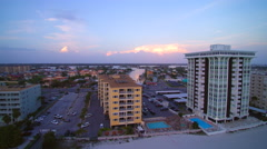 Jib type shot of condos and thunderhead clouds in distance Stock Footage