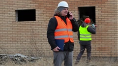 Site manager talking on smart phone and worker with sledgehammer near boards Stock Footage