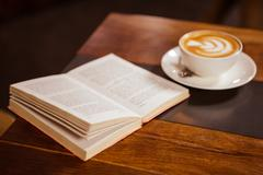 Cup of cappuccino with coffee art and book at coffee shop Stock Photos