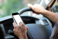 Man using mobile phone while driving a car Kuvituskuvat