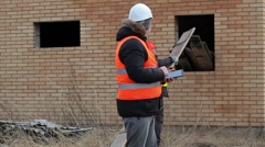 Site manager using tablet PC and worker sorting boards Stock Footage