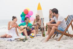 Group of friends having a small party on the beach Stock Photos