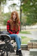 Young grumpy redhead woman red plaid jacket blue jeans sitting on bench Stock Photos