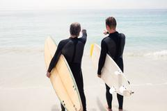 Rear view of father and son standing with surfboard and pointing at a distanc Stock Photos