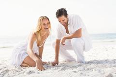 Couple having fun on the beach on a sunny day Stock Photos