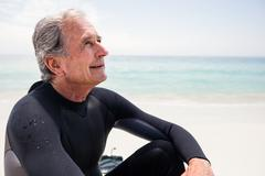Happy senior man in wetsuit sitting on beach and looking up Stock Photos