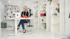 4K Portrait of smiling fashion designer working on laptop computer at her desk - stock footage